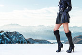 Beautiful legs woman with black shine leather jacket and high heels boots in Italy Swiss Alps mountain.