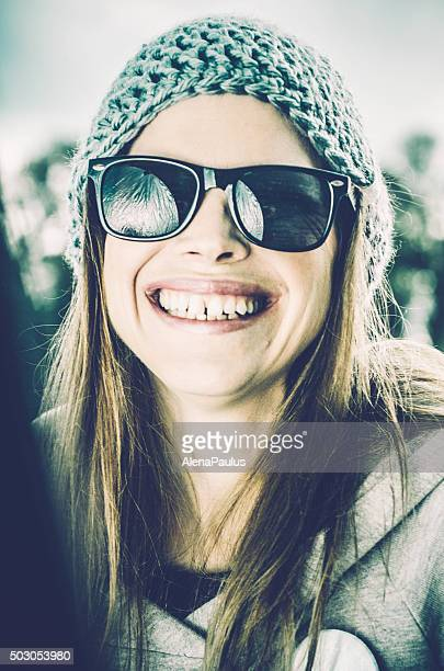 Winter smiling girl with a woolen hat and glasses