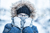 Winter snowy portrait of young girl in warm clothing.