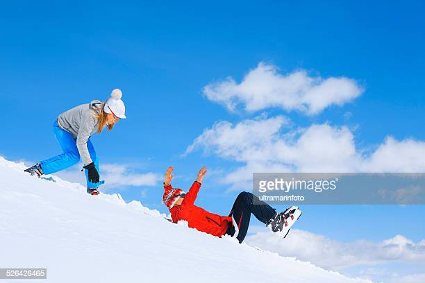 Winter sport  playing, couple men and women snow skiers tobogganing