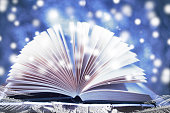 Winter story. Open book on wooden snowy blue background.
