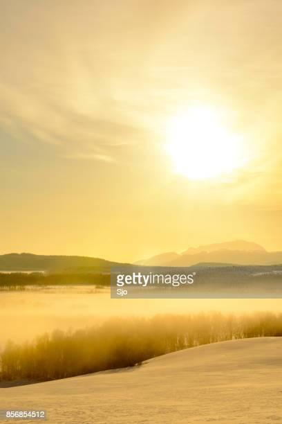 Zonsondergang in de winter over een bevroren besneeuwde landschap in Noorwegen