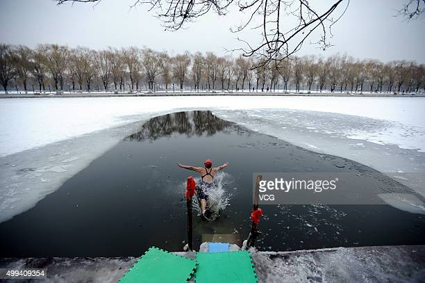 A winter swimmer exercises in a partially frozen lake in Beiling Park on November 1 2015 in Shenyang Liaoning Province of China A group of citizens...