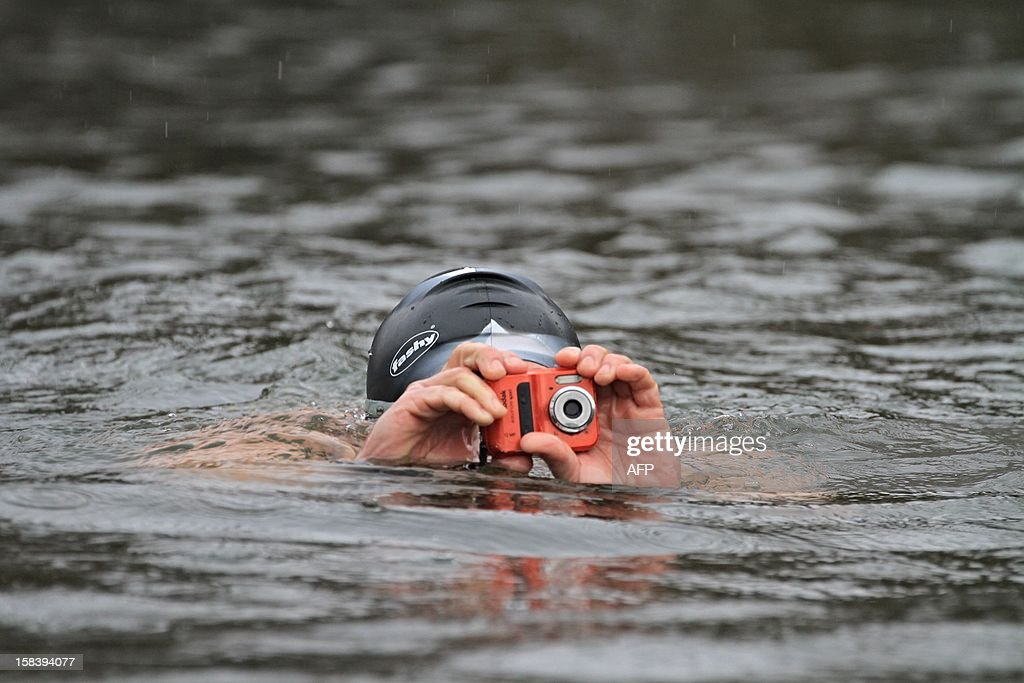 A winter swimmer takes a picture while swimming in the river Thaya near the border to Austria near Breclav, Czech Republic on December 15, 2012. Winter swimmers celebrated the entry of the Czech Republic to the Schengen area on December 21, 2007 and commemorated the victims shot by soldiers in crossing the border to Austria under communism. AFP PHOTO/ RADEK MICA