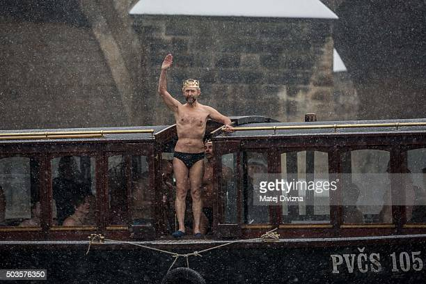 Winter swimmers arrive in the boat for the traditional Three Kings swim in the Vltava river on January 6 2016 in Prague Czech Republic About thirty...