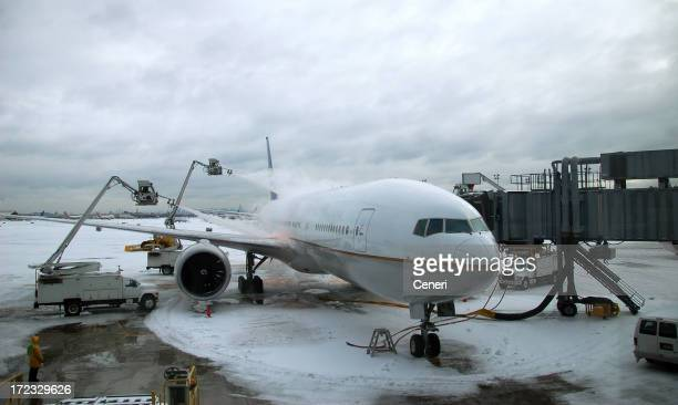 Winter Travel Delay: de-icing an airplane during a blizzard / snowstorm
