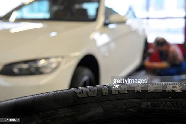 A winter tyre lies next to a car as an employee fits a tyre in a small garage in Ingolstadt southern Germany on November 26 2010 The upper house of...