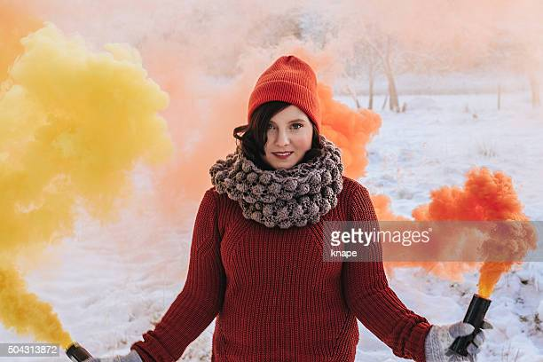 Winter woman with color smoke grenades