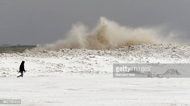 Winter wonderland along Woodbine Beach as a man takes a stroll as waves crash over the frozen rocks People in the GTA dig out after one of the worst...