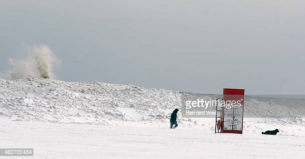 Winter wonderland as a man and his dog take a stroll along Woodbine Beach as the waves crash over the frozen rocks People in the GTA dig out after...