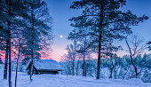 Panoramic view of beautiful winter wonderland scenery with traditional wooden shelter in  scenic evening light at sunset in Scandinavia, northern Europe