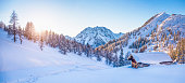 Panoramic view of beautiful winter wonderland mountain scenery with traditional mountain cabin the background in the Alps in golden evening light at sunset.
