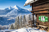 Beautiful view of scenic white winter wonderland mountain scenery in the Alps with traditional wooden mountain chalet on a cold sunny day with blue sky and clouds