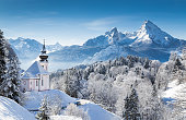 Panoramic view of beautiful winter wonderland mountain scenery in the Bavarian Alps with pilgrimage church of Maria Gern and famous Watzmann massif in the background, Nationalpark Berchtesgadener Land