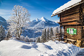 Panoramic view of beautiful winter wonderland mountain scenery in the Alps with traditional mountain chalet on a cold sunny day with blue sky and clouds