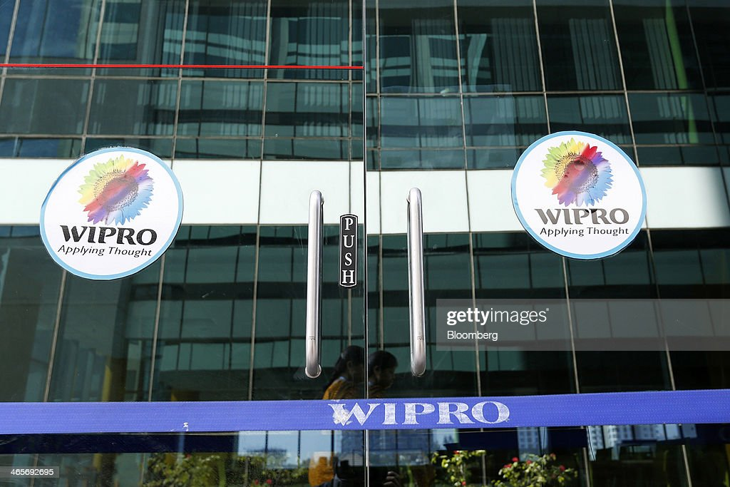 Wipro Ltd. logos are displayed on glass doors at the company's campus in Bangalore, India, on Tuesday, Jan. 28, 2014. Worldwide spending on information technology will grow 3.1 percent to $3.8 trillion this year, with IT services set to climb 4.5 percent, researcher Gartner Inc. forecast Jan. 6. Photographer: Vivek Prakash/Bloomberg via Getty Images