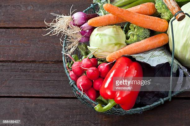 Wire basket with different vegetables on dark wood