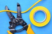 Wire stripper, insulation tape and cable on blue background