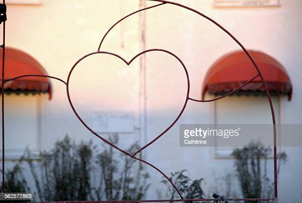 Wired heart at sunset in front of rundown building