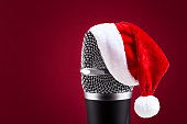 Wireless microphone with santa hat on it closeup on red background