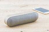 Wireless speaker for mobile phone, Speaker for smartphone on wood desk Background.