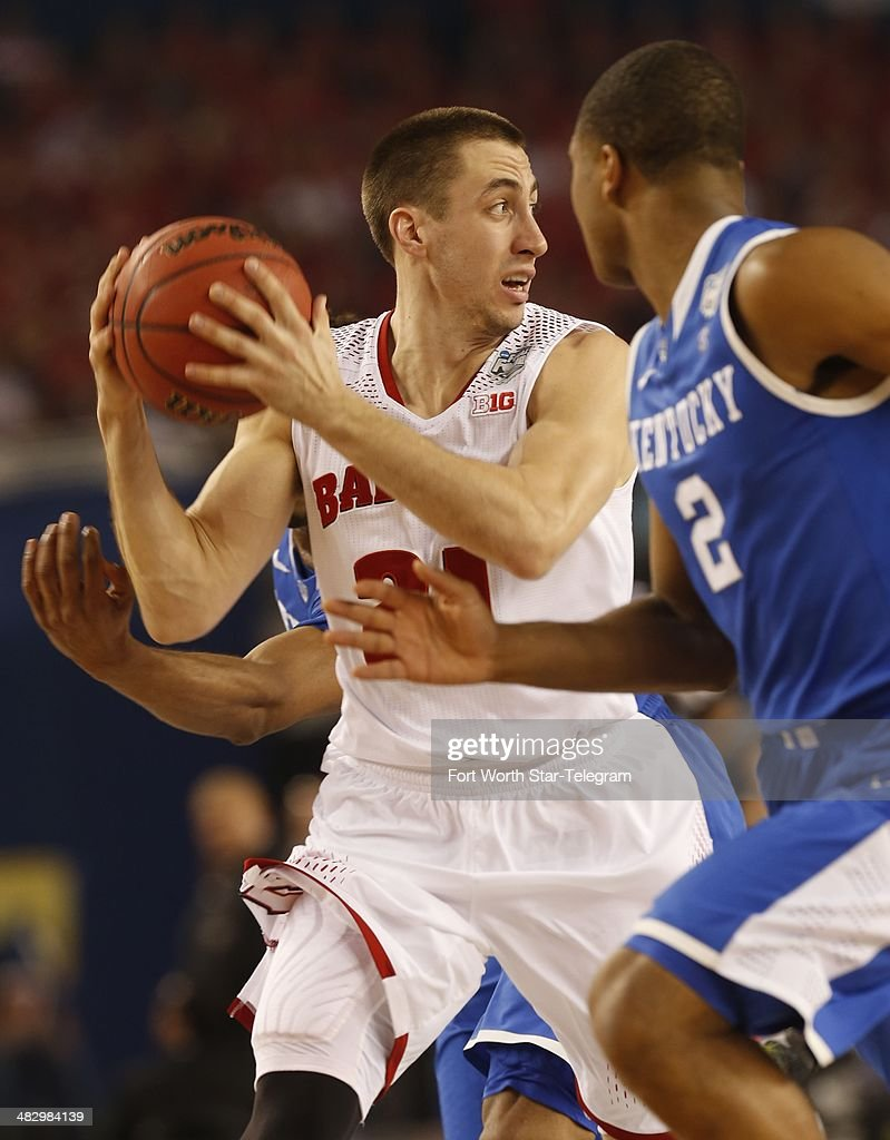 Wisconsin Badgers guard Josh Gasser looks for an outlet while defended by Kentucky Wildcats guard Aaron Harrison during first half action as the...