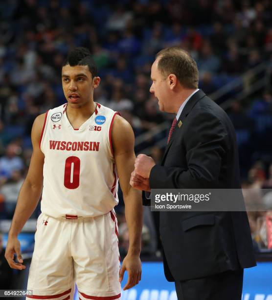Wisconsin Badgers head coach Greg Gard chats with West Virginia Mountaineers guard Teyvon Myers during the NCAA Division 1 Men's Basketball...