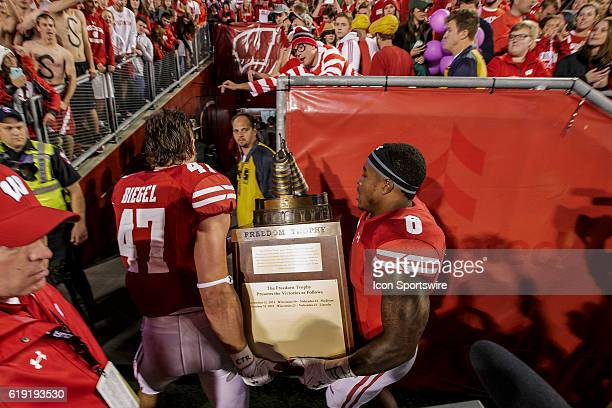 Wisconsin Badgers outside linebacker Vince Biegel and Wisconsin Badgers running back Corey Clement bring back the freedom trophy during an NCAA...