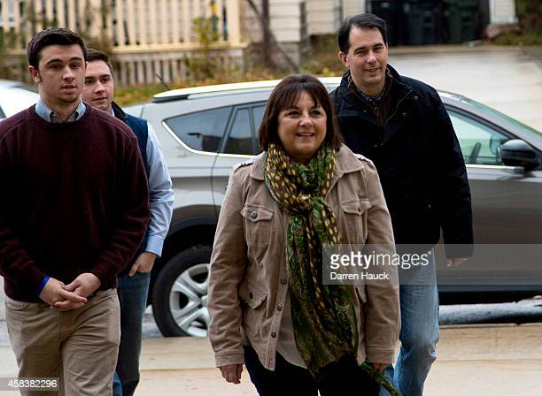 Wisconsin Gov Scott Walker arrives with his wife Tonette center and sons Alex left and Matt second left to casts his ballot on election day at...