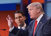 Wisconsin Governor Scott Walker listens as real estate tycoon Donald Trump speaks during the prime time Republican presidential debate on August 6...