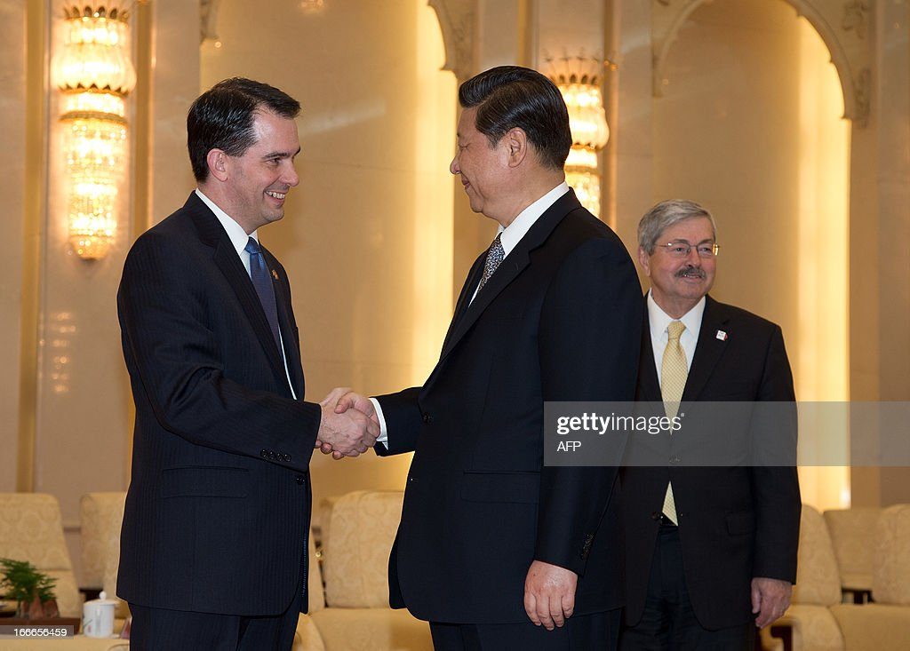 Wisconsin Governor Scott Walker (L) shakes hands with Chinese President Xi Jinping (C) before a meeting as Iowa Governor Terry Branstad (R) looks on at the Great Hall of the People in Beijing on April 15, 2013. Branstad is in China until April 19. AFP PHOTO / POOL / Andy Wong