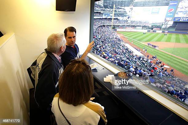 Wisconsin Governor Scott Walker stands in a executive press box before the start of the game between the Colorado Rockies and the Milwaukee Brewers...