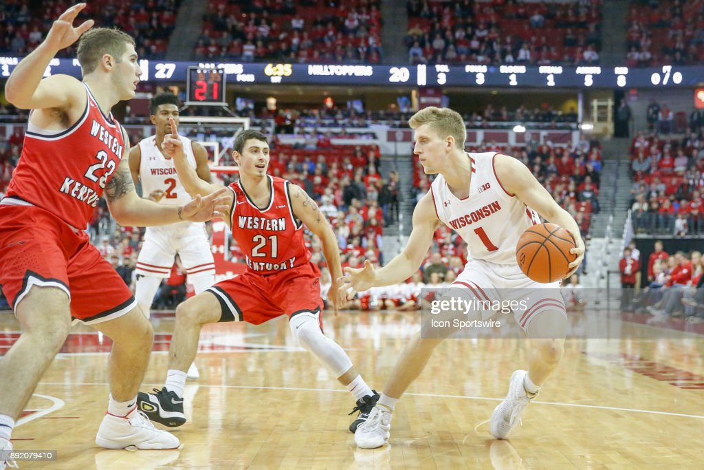 Wisconsin guard Brevin Pritzl(1) looks for an opening through Western Kentucky guard Jake Ohmer (21) and Western Kentucky forward Justin Johnson (23) during a college basketball game between the University of Wisconsin Badgers and the Western Kentucky University Hilltoppers on December 13, 2017 at the Kohl Center in Madison, WI.