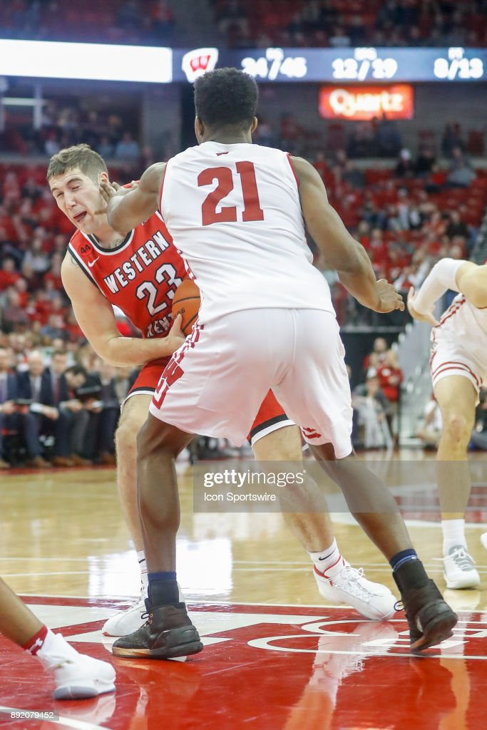 Wisconsin guard Khalil Iverson (21) gets a hand to the face of Western Kentucky forward Justin Johnson (23) during a college basketball game between the University of Wisconsin Badgers and the Western Kentucky University Hilltoppers on December 13, 2017 at the Kohl Center in Madison, WI.