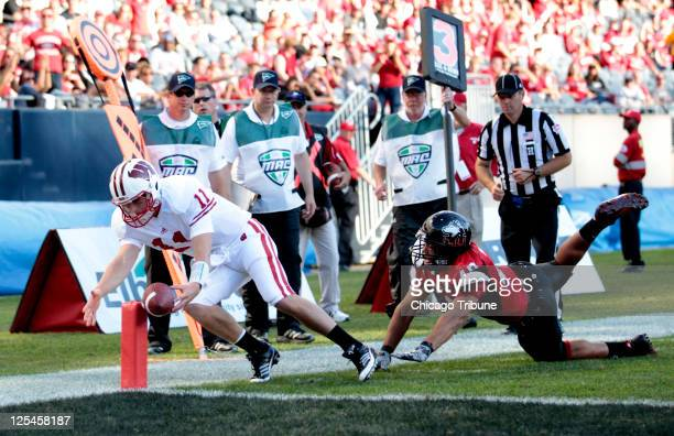 Wisconsin quarterback Joe Brennan scores a touchdown in front of Northern Illinois linebacker Jason Meehan during the fourth quarter at Soldier Field...