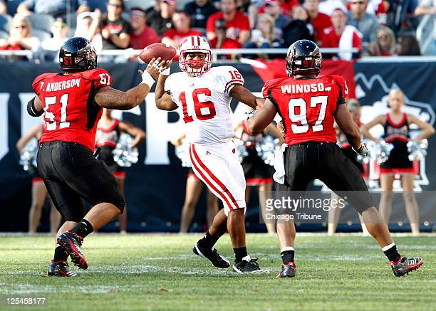 Wisconsin quarterback Russell Wilson makes a pass between left Northern Illinois defensive lineman Zach Anderson and right Northern Illinois Huskies...
