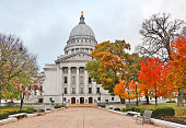 National Historic Landmark city of Madison, Wisconsin, Midwest USA. Autumn view with bright colored trees along path to the entrance and cloudy sky during later afternoon.