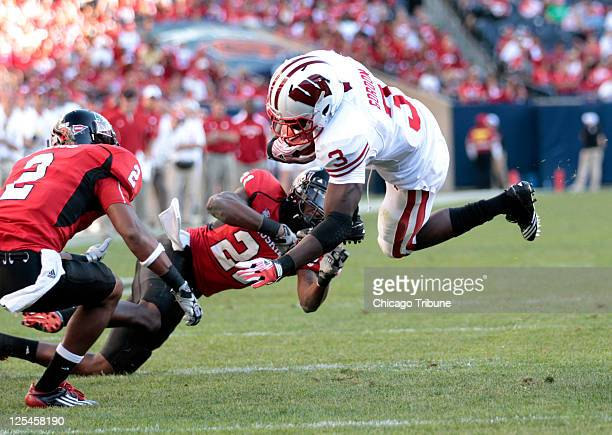 Wisconsin's Melvin Gordon right gains some yardage by leaping over Northern Illinois safety Dechane Durante during the fourth quarter at Soldier...