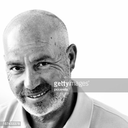 A wise bald happy man posing for a photo