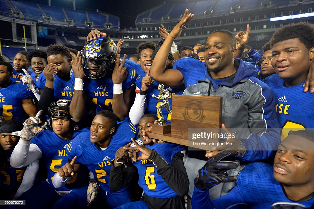 Wise head coach Dalawn Parrish and his team posed for a photograph with the trophy after beating Howard in the Maryland 4A championship game at MT...