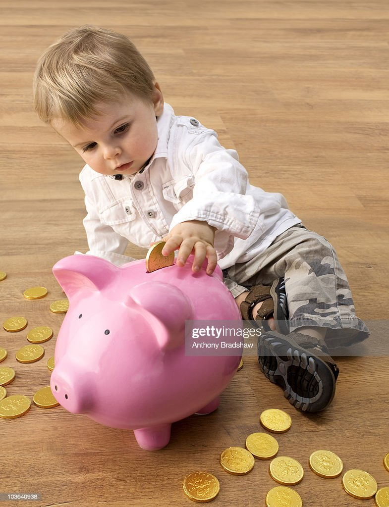 Wise toddler saves for the future : Stock Photo