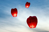 Wish lanterns being released into air.