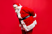 I wish visit chiropractor! Profile side view stylish aged unhealthy spine mature Santa in costume headwear gloves with scoliosis pose with cramp spasm or injury in back isolated noel red background