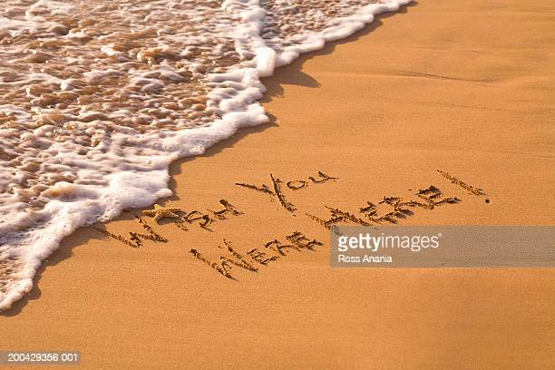 'Wish you were here' written in sand on beach, sunset, elevated view