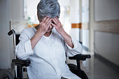 Shot of a senior woman in a wheelchair sitting with her hands over her eyes