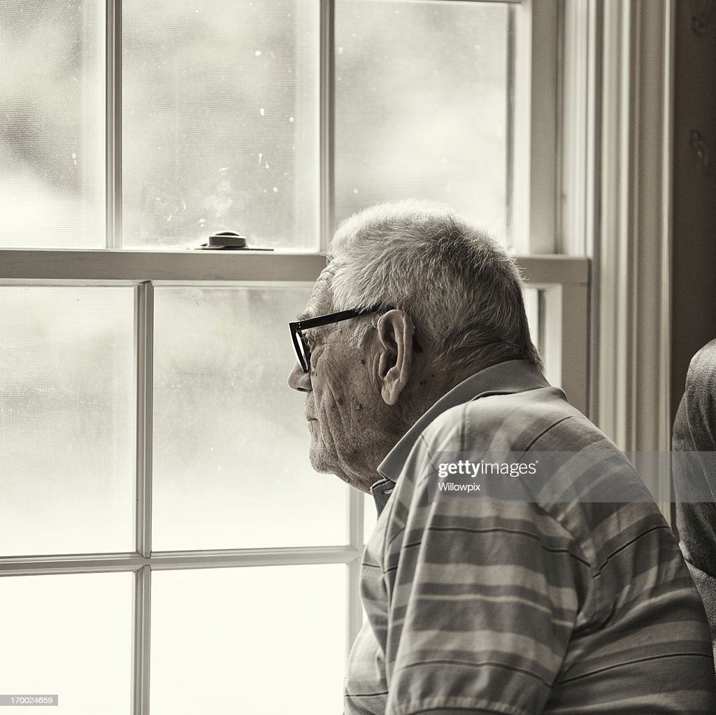 Wistful Senior Man Looking Through Grungy Window : Stock Photo