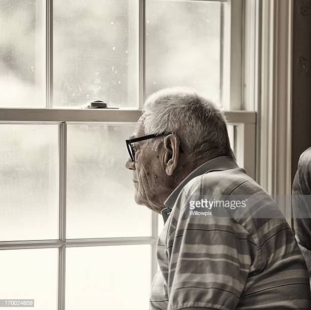 Wistful Senior Man Looking Through Grungy Window