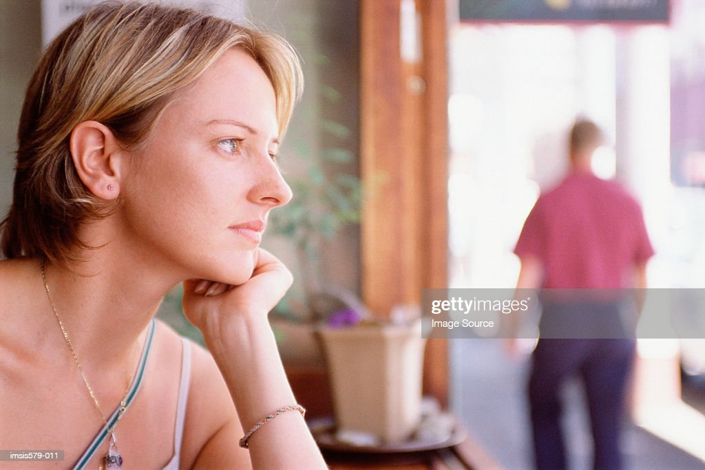 Wistful young woman in cafe : Stock Photo