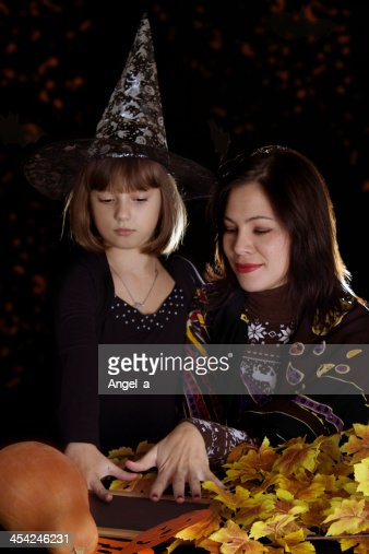 Witch child and mother makong magic on halloween : Stock Photo