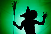 A green and black silhouette of a wicked witch holding her broom.